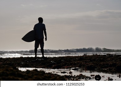 Silhouette at sunset of a surfer on the seashore looking at the horizon before venturing off with his surfboard in the ocean waves. Concept of: extreme sport, vacation.