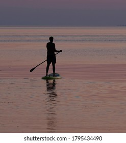 Silhouette of a SUP paddling in the warm sea after the sunset