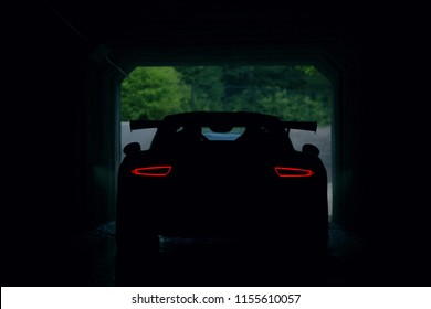 Silhouette of supercar in tunnel with stop lights. Back view of supercar