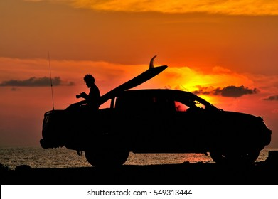 The silhouette of a surfer  and car  during sunrise on the beach