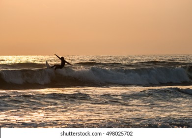 Silhouette, of Surfer catching a wave at sunset on Huntington beach, southern California
