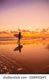 Silhouette with surfer girl and surfboard on a beach at warm sunset or sunrise. Surfer and ocean