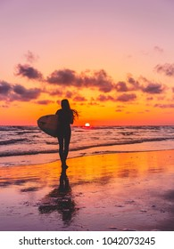 Silhouette of the surfer girl with surfboard on a beach at sunset. Surfer and ocean