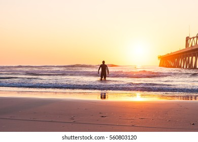 The silhouette of a surfer heading into the water for a surf