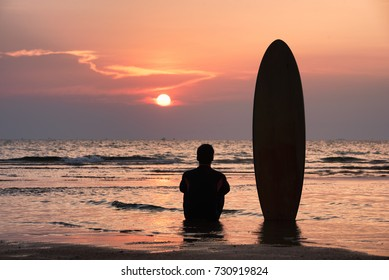 Silhouette of Surfer man sitting alone on the beach looking out to sea with surfboards in the sunset after surfing.