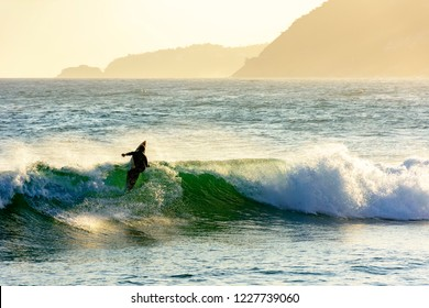 Silhouette of surfer on the beach, by the sea in Ipanema, Rio de Janeiro during sunset