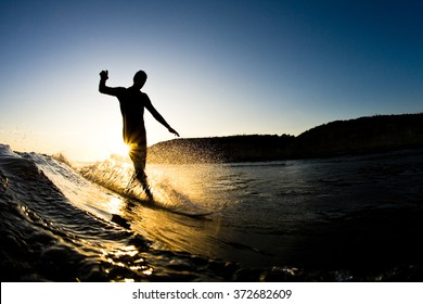 The silhouette of a surfer riding a wave at an empty surf spot