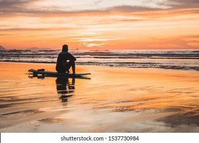 Silhouette of a surfer sitting on the beach of the Atlantic Ocean, near San Sebastian and Bilbao, North of Spain, Europe watching a dramatic stunning colorful sunset
