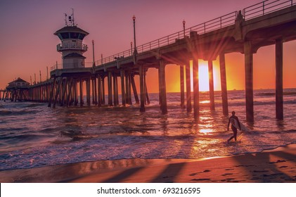 Silhouette of a surfer at sunset in front of the Huntington Beach Pier in California