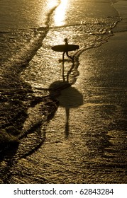 silhouette of surfer walking into the sea