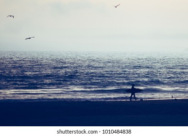 Silhouette, of Surfer walking on the beach at sunset. San Simeon beach, southern California
