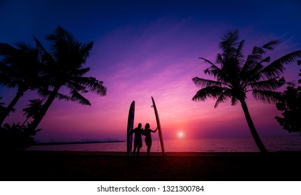 Silhouette of surfers couple holding long surf boards at sunset on tropical beach. Background
