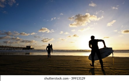 silhouette of surfers at sunset