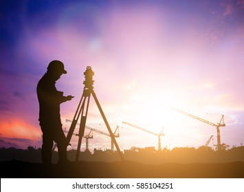 silhouette survey engineer working  in a building site over Blurred construction worker on  Industrial site