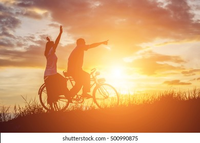 silhouette of sweet young couple in love happy time on bicycle