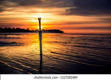 Silhouette of the sword in front of the sunset. Isolated background, orange, yellow color.