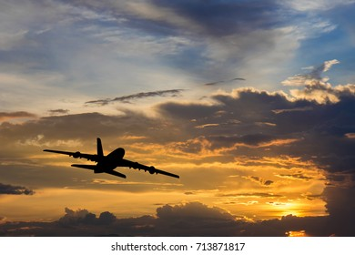 Silhouette from a take off plane that is flying form the airport. Photo taken during a nice colorful sunset.