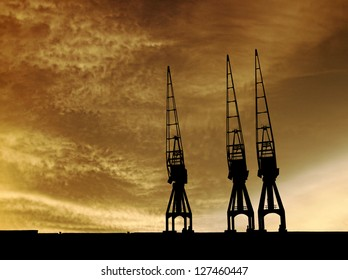 Silhouette of tall gantry cranes along a dock against a surreal apocalyptic evening sky.