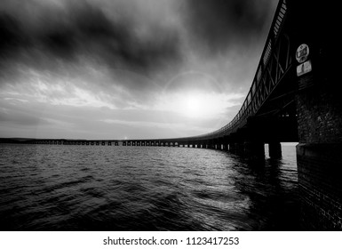 Silhouette of The Tay Rail Bridge on the river Firth of Tay, textured with stormy sky and lens flare in black and white for a mystic feeling, near Dundee in Angus Council, Scotland.
