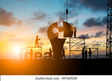 Silhouette Team business engineer work connecting jigsaw puzzle piece together team responsible for the idea of progress Teamwork potential and motivate employee growth concept over blurred natural