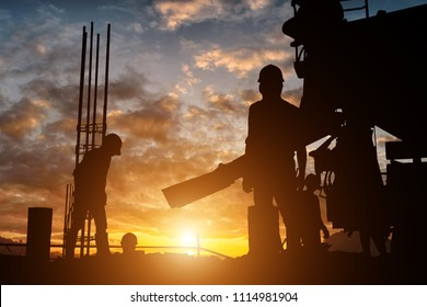 Silhouette team of business engineers are working hard. The construction site is not clear at sunset time.