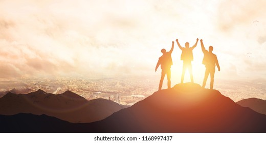 Silhouette of the team on the mountain against the backdrop of the city. Leadership Concept