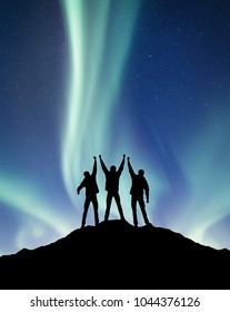 Silhouette of a team on the northen light backgroun. Concept and idea of active life