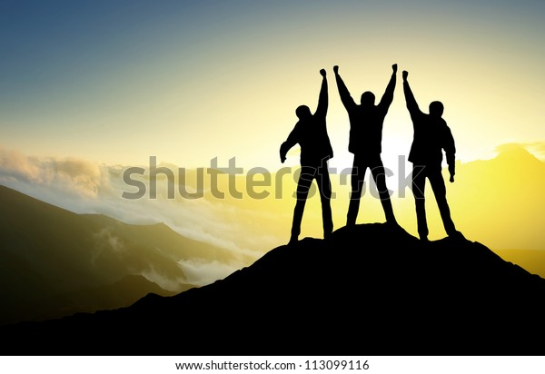 Silhouette of the team on the peak of mountain. Sport and active life