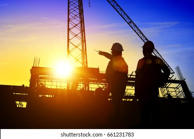 Silhouette Teams Businessman engineer looking blueprint in a building site over Blurred construction site at sunset