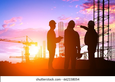 Silhouette Teams engineer looking construction worker in a building site at sunset