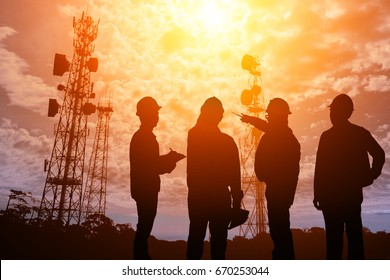 Silhouette Teams engineer looking Telecommunication mast television antennas on sunlight
