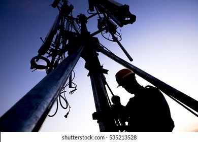Silhouette of Technician working on communication towers in the dusk