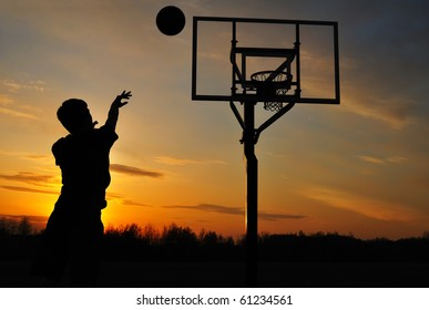 Silhouette of Teen Boy Shooting a Basketball at Sunset