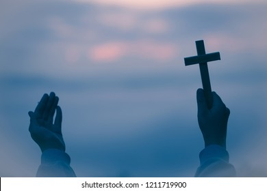 Silhouette of teen girl hands holding wooden cross on sunrise background, Crucifix, Symbol of Faith.