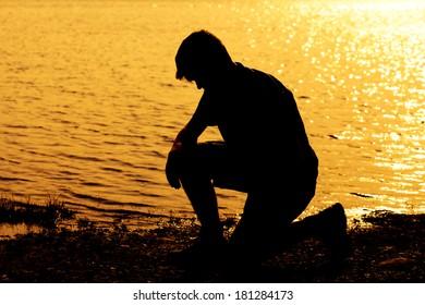 Silhouette of teenage boy kneeling down