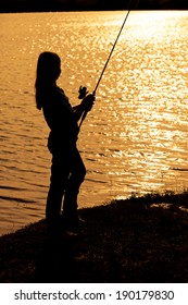 Silhouette of a teenage girl fishing at sunset