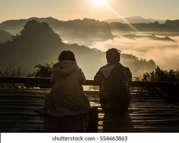 silhouette teenager lovers couple over natural background at the mountain  looking in the Sun rise :black shadow loving people hug and kiss:love and valentines concept.