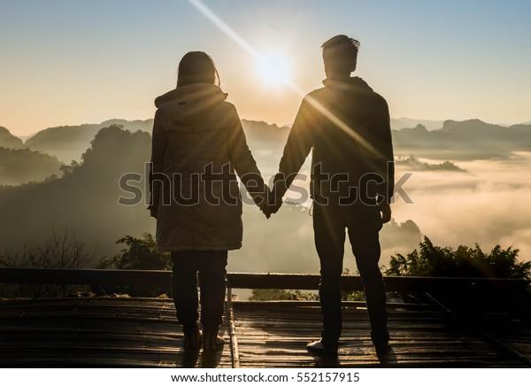 Silhouette Teenager Liebhaber paaren auf natürlichem Hintergrund am Berg und halten Hände Blick in die Sonne : schwarze Schatten liebenden Menschen Umarmung und Kuss:Liebe und Valentinkonzept.