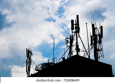 Silhouette Telecommunication mobile antenna and satellite dish on roof building. communication network technology concept.