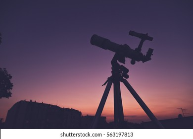Silhouette of a telescope on a morning / evening sky.