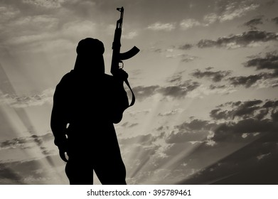 Silhouette of  terrorist with a weapon against a background of a sunset