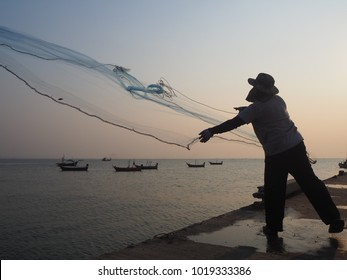 Silhouette of Thai fisherman stand on the harbor bridge for casting a net for catching salt water fish in gulf of Thailand sea in the evening before sunset.