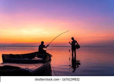 Silhouette of Thailand fisherman on wooden boat .