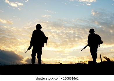 Silhouette of Thailand soldier walking patrol and holding gun at sunset