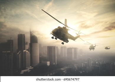 Silhouette of three army helicopters doing patrols while flying over downtown, shot at sunset time