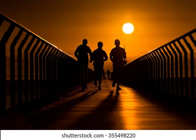 Silhouette of three backlit runners running towards the rising sun at the end of pier.
