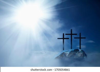 Silhouette of three crosses on a rocky hill against dramatic sky background and symbolize the Crucifixion and resurrection of Jesus Christ.