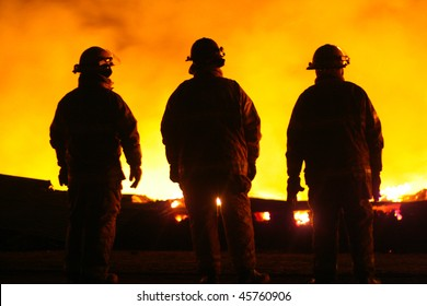 A silhouette of three Fire Fighters watching a fire