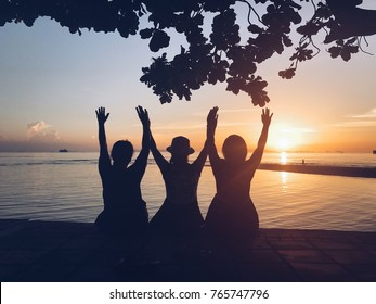 Silhouette of three friends in the morning at the beach looking at sunrise . Support, together, winning, helping, freedom concept.