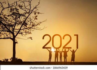 Silhouette von drei Generationen Familie, die 2021 Zahlen hält, während sie in der Nähe eines Baumes im Park steht. Aufnahme zur Sonnenaufgangszeit